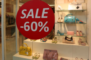 Show-window of shoe shop during seasonal sale.