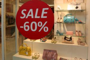 Show-window of shoe shop during seasonal sale.